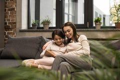 retrato do livro de leitura novo da mãe e da filha junto ao descansar no sofá imagens de stock