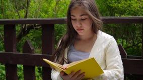 Retrato do livro de leitura sério do adolescente e do assento de inclinação de giro da página no banco na floresta na mola filme