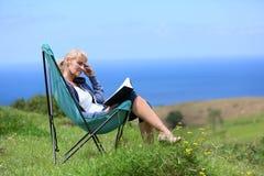 Retrato do livro de leitura superior da mulher na cadeira de acampamento pelo mar Imagem de Stock