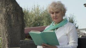 Retrato do livro de leitura superior da mulher no parque video estoque