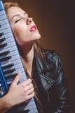 Retrato do músico bonito da jovem mulher atrás do teclado que olha acima Fotos de Stock