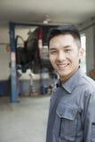 Retrato do mecânico de sorriso da garagem foto de stock