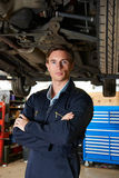 Retrato do mecânico Standing Under Car Foto de Stock Royalty Free