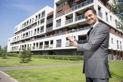 Retrato do mediador imobiliário de sorriso que apresenta o prédio de escritórios Imagem de Stock