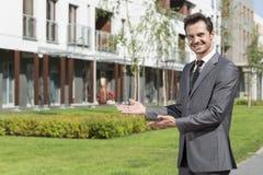 Retrato do mediador imobiliário feliz que apresenta o prédio de escritórios foto de stock