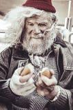 Retrato do mendigo que toma o bolo que encontrou para o café da manhã imagem de stock