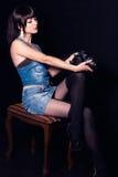 Retrato do meninas bonitas novas com a câmera em um fundo preto no estúdio Imagem de Stock Royalty Free