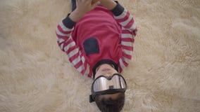 Retrato do menino afro-americano adorável que encontra-se no assoalho no tapete macio bege com os óculos de proteção do esqui vídeos de arquivo