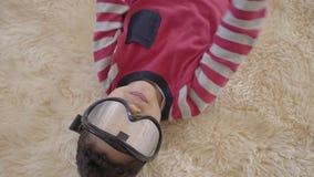Retrato do menino afro-americano pequeno que encontra-se no assoalho no tapete macio bege com os óculos de proteção do esqui e video estoque