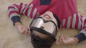 Retrato do menino afro-americano pequeno que encontra-se no assoalho no tapete macio bege com vidros do paintball em seus olhos filme