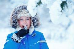 Retrato do menino bonito da criança que tenta comer fora a neve Criança que tem o divertimento em um parque do inverno Imagens de Stock Royalty Free
