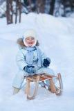 Retrato do menino bonito em um pequeno trenó no inverno Imagem de Stock