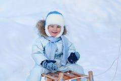 Retrato do menino bonito em um pequeno trenó no inverno Foto de Stock Royalty Free