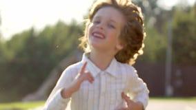 Retrato do menino bonito pequeno louro que corre no dia e no sorriso de verão Criança que tem o ar livre do divertimento fora do  filme