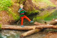 Retrato do menino bonito que cruza o rio no verão Fotografia de Stock Royalty Free
