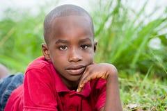 Retrato do menino bonito que encontra-se em ervas verdes frescas imagens de stock royalty free