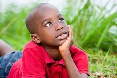 Retrato do menino bonito que encontra-se em ervas verdes frescas fotografia de stock