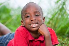 Retrato do menino bonito que encontra-se em ervas verdes frescas foto de stock royalty free