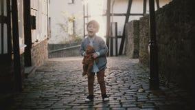 Retrato do menino caucasiano bonito que canta fora Criança masculina que olha a câmera na rua pavimentada antiga da cidade Alarga video estoque