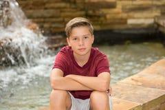 Retrato do menino considerável pela fonte Fotografia de Stock