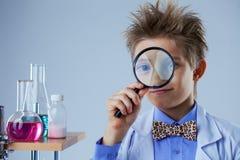 Retrato do menino curioso que olha através da lente de aumento Fotografia de Stock Royalty Free