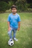 Retrato do menino da virada que está com a bola de futebol no parque Fotografia de Stock Royalty Free