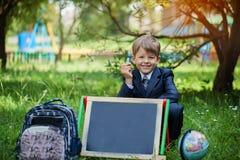 Retrato do menino de escola bonito no parque, dia ensolarado fotos de stock royalty free