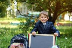 Retrato do menino de escola bonito no parque, dia ensolarado foto de stock royalty free