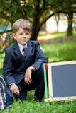 Retrato do menino de escola bonito no parque, dia ensolarado imagens de stock