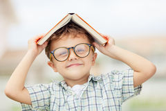 Retrato do menino de escola bonito que olha o ar livre muito feliz em Foto de Stock