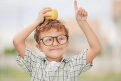 Retrato do menino de escola bonito que olha o ar livre muito feliz em Imagem de Stock Royalty Free