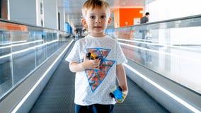 Retrato do menino de sorriso da criança que está na escada rolante no terminal de aeroporto foto de stock royalty free