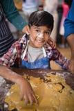 Retrato do menino de sorriso que prepara o alimento na cozinha foto de stock