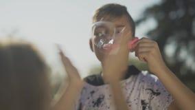 Retrato do menino na camisa vermelha que funde uma bolha de sabão no parque As mãos da criança estão estalando bolhas de sabão Mo filme