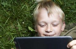 Retrato do menino novo louro da criança que joga com uma tabuleta digital Foto de Stock