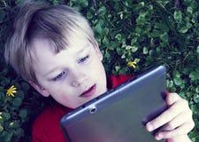 Retrato do menino novo louro da criança que joga com uma tabuleta digital Imagem de Stock Royalty Free