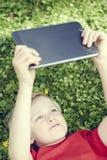 Retrato do menino novo louro da criança que joga com uma tabuleta digital Foto de Stock Royalty Free