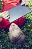 Retrato do menino novo louro da criança que joga com uma tabuleta digital Imagens de Stock Royalty Free