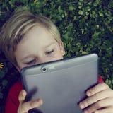 Retrato do menino novo louro da criança que joga com uma tabuleta digital Imagem de Stock