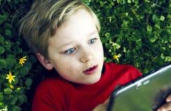 Retrato do menino novo louro da criança que joga com uma tabuleta digital Imagens de Stock