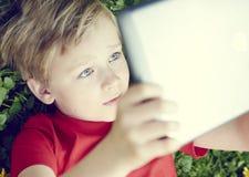Retrato do menino novo louro da criança que joga com uma tabuleta digital Fotografia de Stock