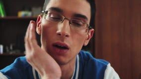 Retrato do menino novo no olhar sério dos vidros na tela Guarde a mão no mordente estudante furar tired filme