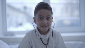 Retrato do menino pequeno bonito com o estetoscópio em suas orelhas que olham in camera de sorriso Cuidados médicos, estilo de vi video estoque