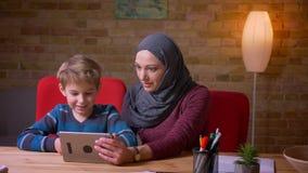 Retrato do menino pequeno e de sua mãe muçulmana em desenhos animados de observação do hijab na tabuleta junto e discutindo os filme