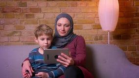 Retrato do menino pequeno e de sua mãe muçulmana no filme de observação do hijab na tabuleta que senta-se no sofá em casa filme
