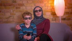 Retrato do menino pequeno e sua de mãe muçulmana no hijab nos vidros 3D que riem ao olhar a comédia na tevê em casa video estoque