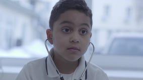 Retrato do menino pequeno pensativo engraçado bonito com o estetoscópio em suas orelhas que olham ao redor Cuidados médicos, esti video estoque