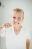 Retrato do menino que sorri ao escovar os dentes fotografia de stock