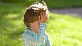 Retrato do menino triste pequeno louro caucasiano que grita e que olha a câmera com rasgos Criança da criança que grita no parque filme