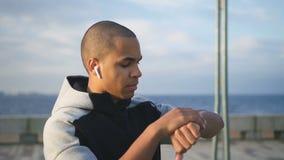 Retrato do modelo afro-americano novo do homem da raça misturada que olha na tela de seu dispositivo esperto onde aplicação vídeos de arquivo